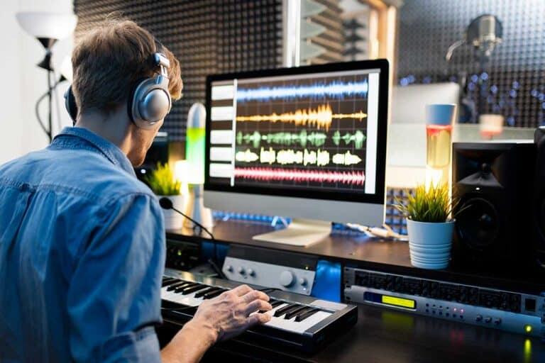 musician-with-headphones-pressing-keys-of-piano-keys