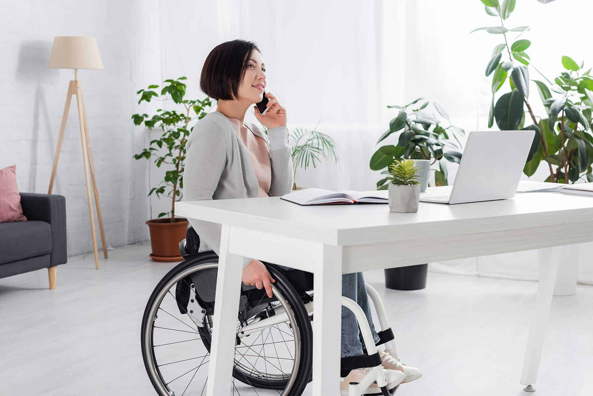 Women in wheelchair on phone with laptop